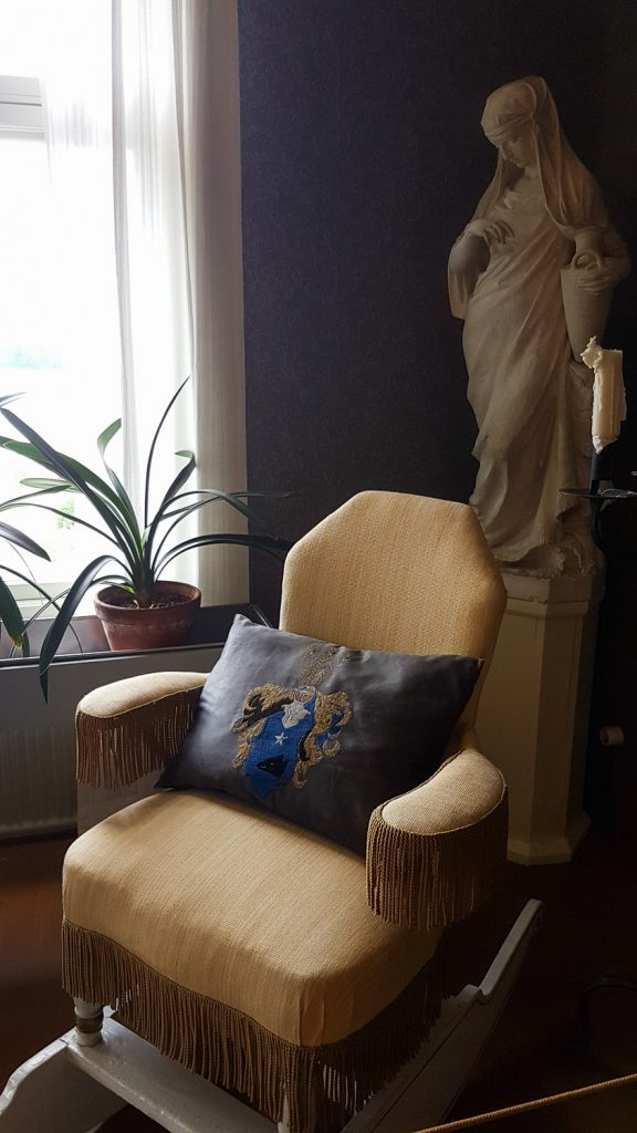 nojatuoli ikkunan edessä ja ikkunalla viherkasveja