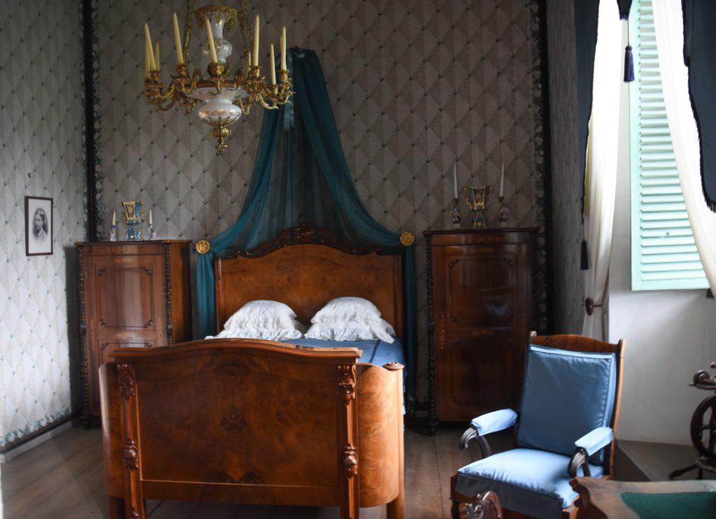 huone, jossa on sänky, kaksi pientä lipastoa ja tuoli, tekstiilit ovat sinisiä
